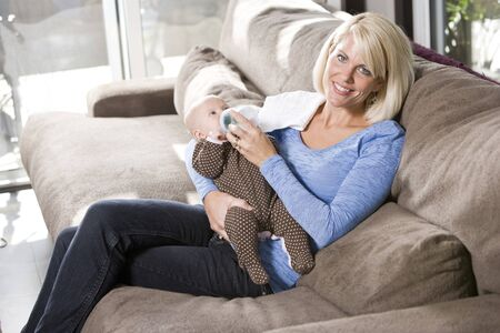 Mom feeding bottle to 3 month old baby at home on couch Stock Photo - 7018849