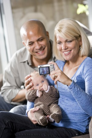 Parents with 3 month old baby on lap at home, mom holding camera photo