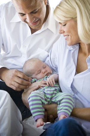 Loving parents holding 3 month old baby sound asleep in arms photo