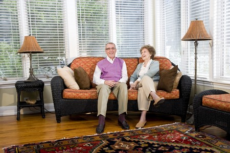 Happy senior couple sitting together on living room couch Stok Fotoğraf