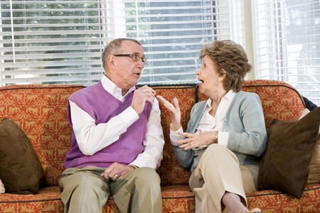 Senior couple talking together on living room couch