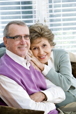 Portrait of happy affectionate senior couple on couch