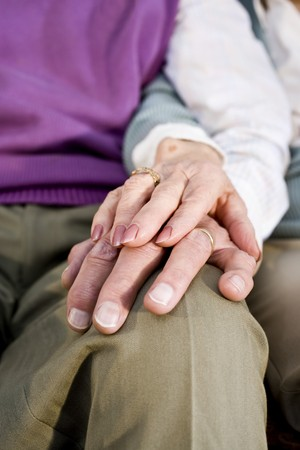 Close-up detail of hands of senior couple touching and resting on knee photo