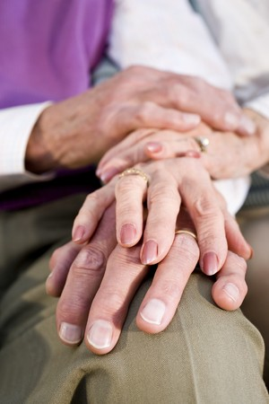 aged care: Close-up detail of hands of senior couple touching and resting on knee Stock Photo