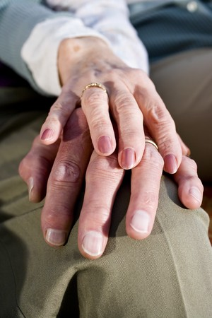 couple holding hands: Close-up detail of hands of senior couple touching and resting on knee Stock Photo