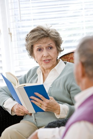 Happy elderly couple sitting on living room couch, focus on woman holding book photo