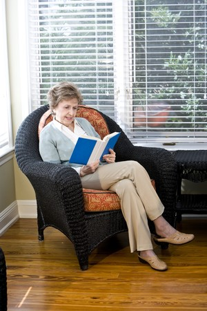 Senior woman sitting on living room chair reading book photo