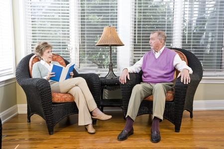 Senior couple sitting on living room chair reading and chatting photo
