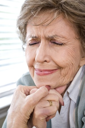 Face of upset elderly woman in 70s with eyes closed photo