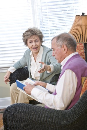 Senior couple chatting in living room reading book, focus on woman talking photo