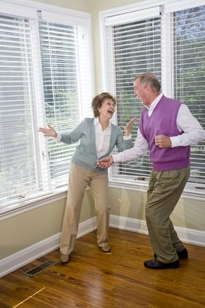 Senior couple having fun dancing in living room photo