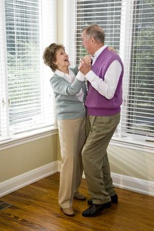stores: Heureux couple senior danser ensemble dans la salle de s�jour