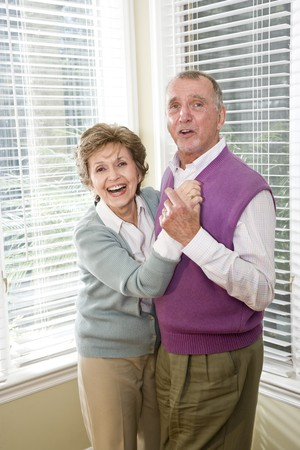 Happy senior couple dancing together in living room photo