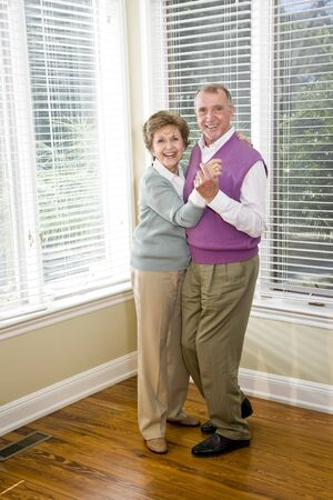 Happy senior couple dancing together in living room Stock Photo - 7181873
