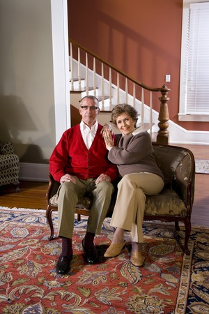 Portrait of senior couple at home in living room sitting on sofa photo