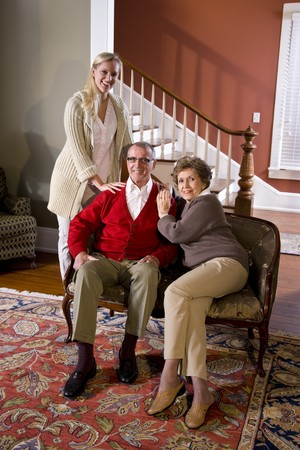 Portrait of senior couple at home on sofa with adult daughter photo