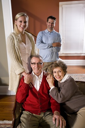 Portrait of senior couple at home on sofa with adult children Stock Photo - 7181896