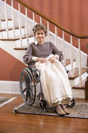 Elderly woman in 70s at home sitting in wheelchair