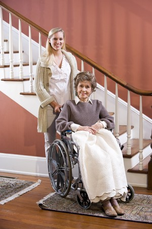 Elderly woman in 70s in wheelchair at home with nurse photo