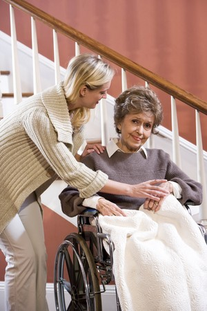 Elderly woman in 70s in wheelchair at home with nurse Stock Photo - 7181880