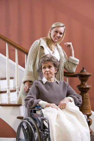 Elderly woman in 70s in wheelchair at home with nurse Stock Photo - 7181849
