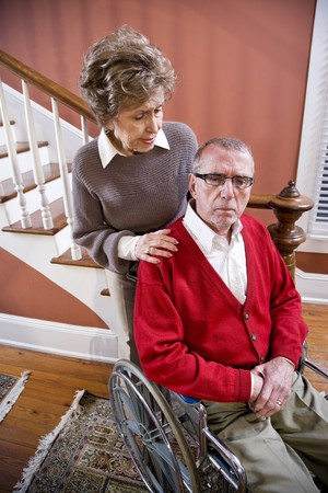 Serious senior couple at home, man in wheelchair photo