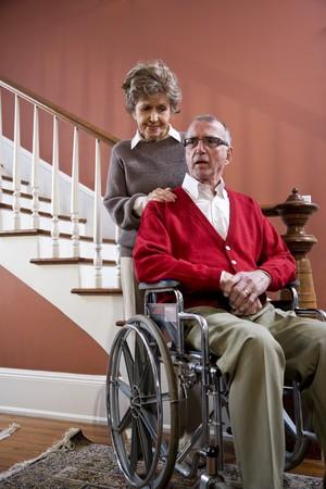Serious senior couple at home, man in wheelchair photo