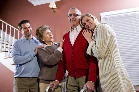 Elderly couple at home with adult children, senior man using walker photo