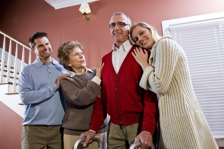 aging: Elderly couple at home with adult children, senior man using walker