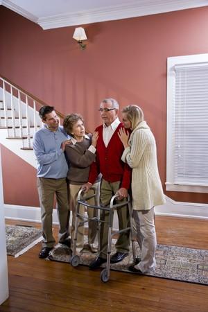 Elderly couple at home with adult children, senior man using walker