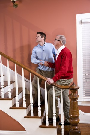 Man helping senior father climb staircase at home