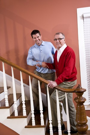 Man helping senior father climb staircase at home photo