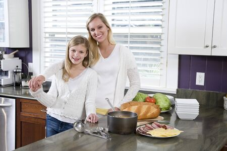 Happy mother and daughter in kitchen making lunch photo