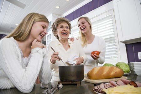 three generation: Three generation family in kitchen serving lunch, talking and laughing Stock Photo