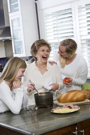 Three generation family in kitchen serving lunch, talking and laughing Stock Photo - 7181759