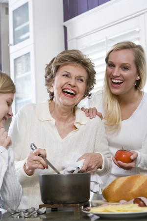 Three generation family in kitchen serving lunch, talking and laughing Stock Photo