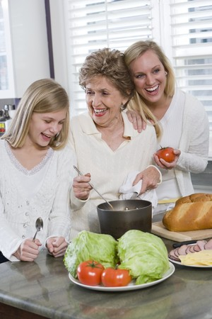 Three generation family in kitchen serving lunch, talking and laughing Stock Photo - 7181792