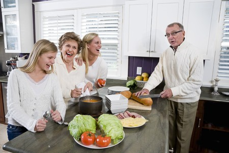 three generations of women: Three generation family in kitchen serving lunch, talking and laughing Stock Photo