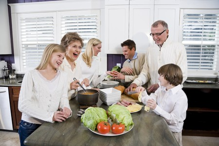 Three generation family in kitchen serving lunch, talking and laughing photo