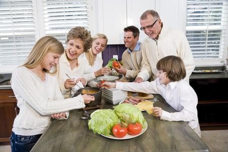 Drie-generatie familie in de keuken serveert lunch, praten en lachen  Stockfoto