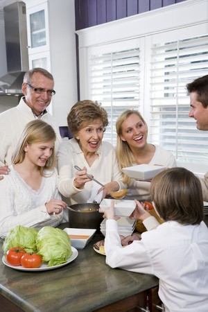 Three generation family in kitchen eating lunch, talking and laughing photo
