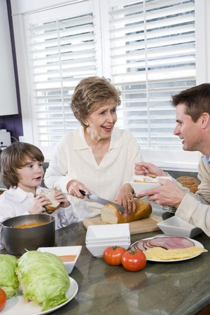 Three generation family in kitchen eating lunch, talking and laughing Stock Photo - 7181762