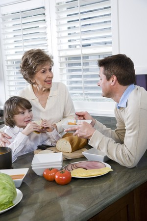Three generation family in kitchen eating lunch, talking and laughing