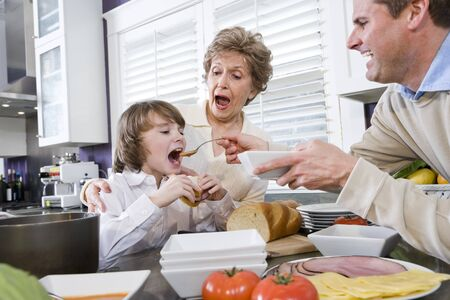 Three generation family in kitchen eating lunch, talking and laughing Stock Photo - 7181775