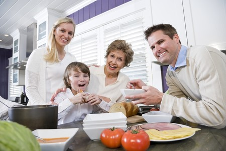 three generation: Three generation family in kitchen eating lunch, talking and laughing