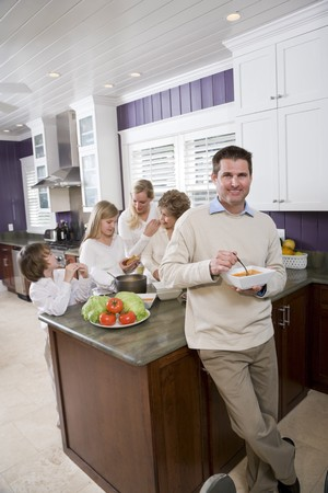 Mid-adult man eating lunch in kitchen with family in background Stock Photo - 7181754
