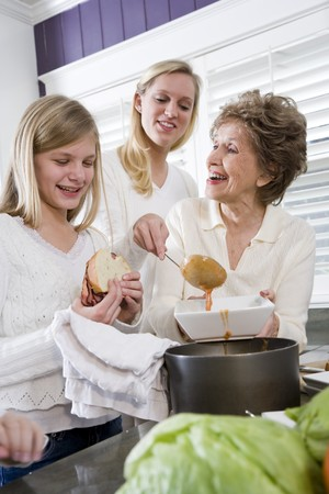 three generations: Three generation family at home serving lunch, home-cooked meal Stock Photo