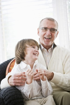 Portrait of 9 year old boy laughing with grandfather photo