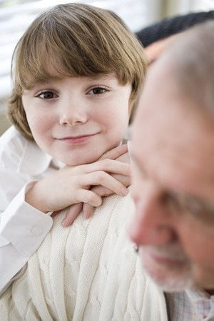 Portrait of smiling boy with his grandfather, leaning on shoulder photo