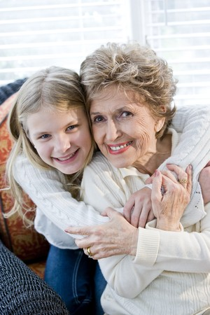 grandmother grandchild: Portrait of happy young girl hugging grandmother at home